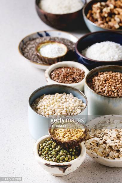 Variety of raw uncooked grains superfood cereal chia seeds linen sesame mung bean walnuts tapioca wheat buckwheat oatmeal coconut rice in ceramic...