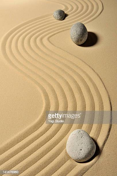 A variety of stones and wave pattern in the sand p