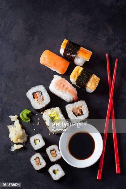 variety of sushi with wasabi, ginger and bowl of soy sauce on dark ground - wasabi stock pictures, royalty-free photos & images