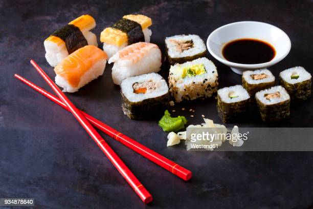 variety of sushi with wasabi, ginger and bowl of soy sauce on dark ground - soy sauce stock photos and pictures