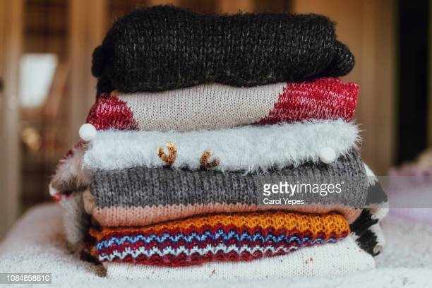 variety of sweaters piled up. - knitted stock pictures, royalty-free photos & images