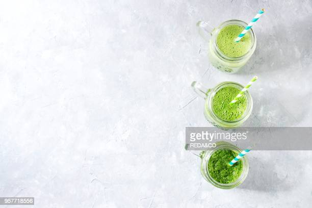 Variety of three color green spinach kale apple yogurt smoothie in mason jars in row with retro cocktail tubes over gray background Healthy vegan...
