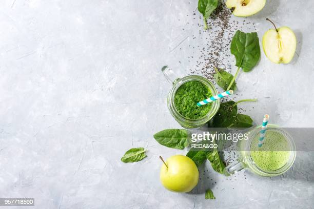 Variety of three color green spinach kale apple yogurt smoothie in mason jars with retro cocktail tubes and ingredients above over gray texture...