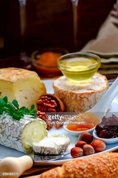 Variety of Ukrainian artisanal soft cheeses: Valoc, Blan, Premiera with cranberry sauce, honey, mint, peach confiture, walnuts, hazelnuts, sesame bread and wine