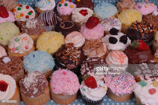A variety of vanilla & chocolate cupcakes with toppings of sprinkles, strawberries, blackberries, pretzels, coconut, chocolate, candy beads
