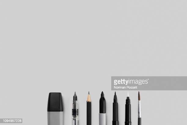 variety of writing and drawing instruments in a row on gray background - matita foto e immagini stock
