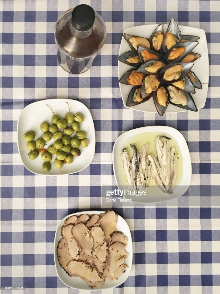 Varios dishes of food and a bottle of wine on a table with blue checked tablecloth : Foto de stock