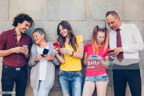 Various ages people texting and sharing outdoors