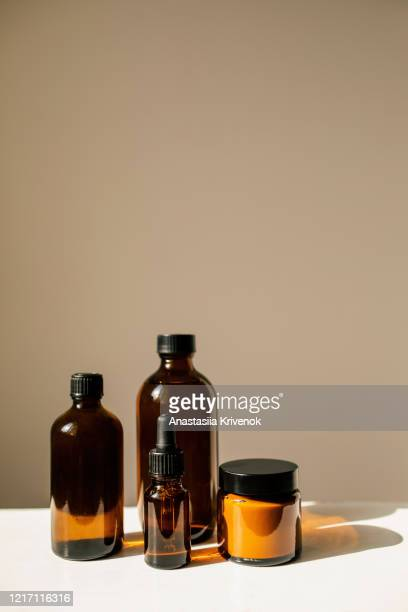 various amber glass bottles for cosmetics, natural skincare and essential oil aromatherapy, or other liquids on beige background. herbal alternative medicine. copy space. - brown stock pictures, royalty-free photos & images