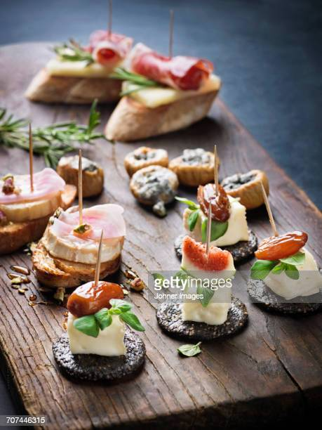various appetizers on wooden board - tapas stock photos and pictures