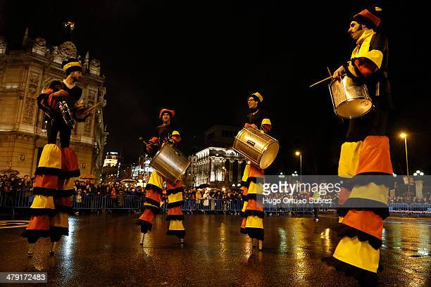 Various artists mounted on stilts playing drums while walking on a sidewalk during the inaugural parade of the Madrid Carnival. Thousands of people...