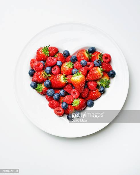 Various berries in a heart shaped bowl