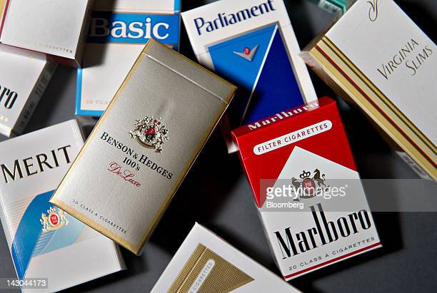 Various brands of Philip Morris International Inc cigarettes packs including Benson Hedges Marlboro Parliament and Virginia Slims are arranged for a...