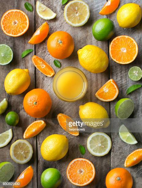various citrus fruits and juice in drinking glass on rustic wooden table top. - zitrusfrucht stock-fotos und bilder