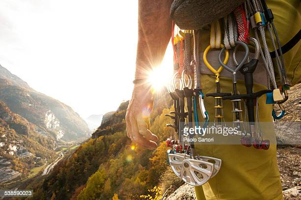 various climbing gear including friends and nuts hanging on a climbers harness, backlit by the sun. cadarese, ossola, italy. - climbing equipment stock pictures, royalty-free photos & images