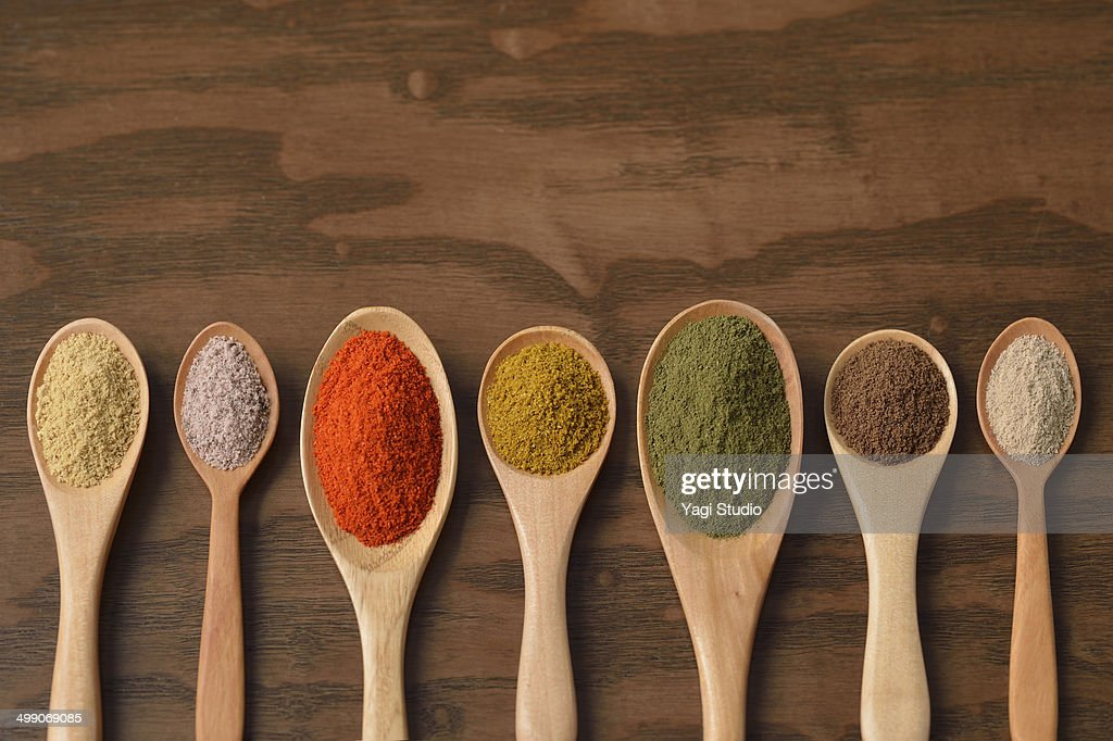 Various colorful spices on wooden spoons : Stock Photo