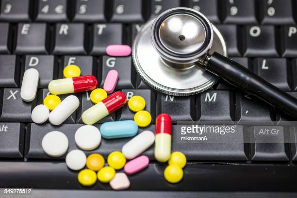 various, coloured capsules and tablets and stethoscope on laptop computer.  medical concept - hypochondria stock photos and pictures