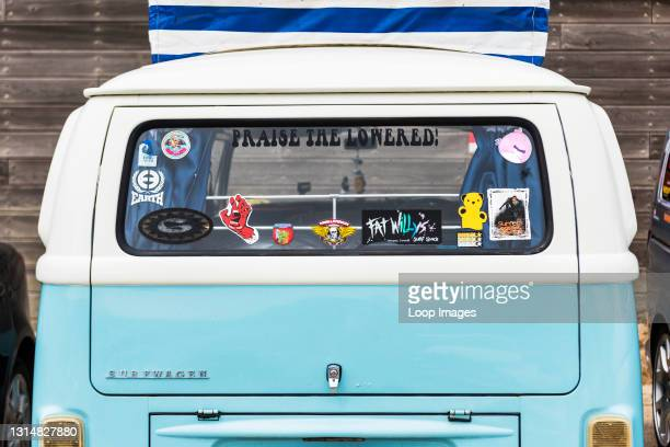Various colourful stickers on the rear window of a Volkswagen Surfwagen vehicle parked at Fistral in Newquay in Cornwall.