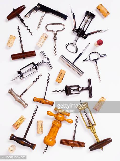 Various corkscrews and corks on white background, overhead view