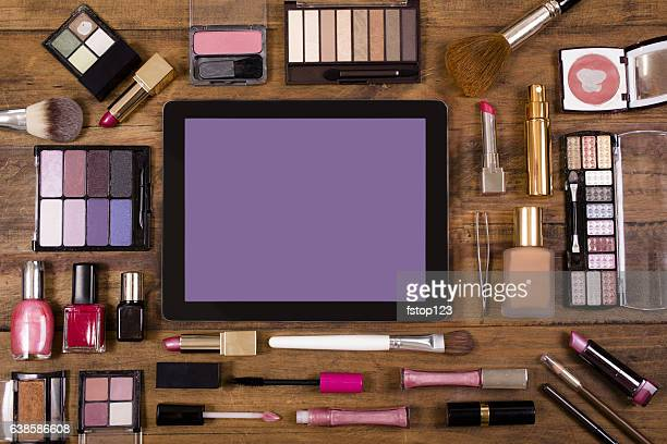 Various cosmetics surround a digital tablet on dressing table.