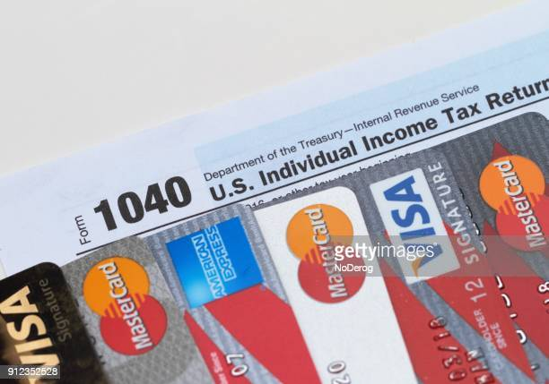 various credit cards on top of a usa 1040 tax form - irs stock photos and pictures