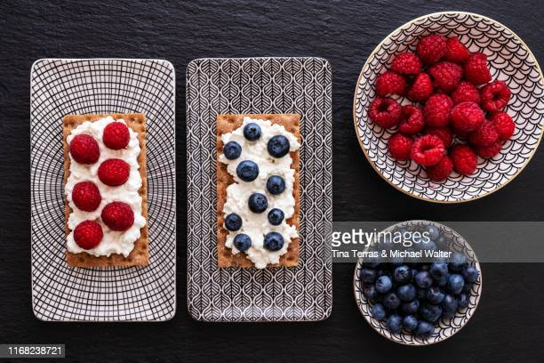 various crispbread biscuits with cream cheese and fruits. blueberries, raspberries and grapes. - tina terras michael walter stock-fotos und bilder