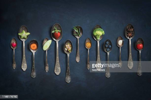 various cut vegetables and fruits in vintage spoons still life. - still life foto e immagini stock