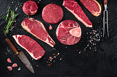 Various cuts of meat, shot from the top on a black background with salt, pepper, rosemary and knives, with copy space