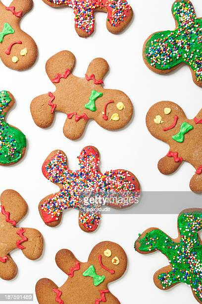 Various decorated gingerbread men cookies arranged on a white background