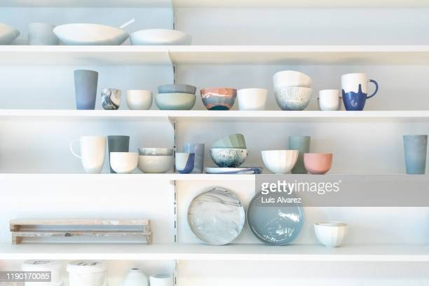 various earthenware on rack in pottery studio - hausdekor stock-fotos und bilder