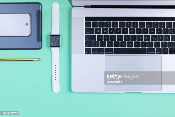 Various electronic devices and a pencil on green ground