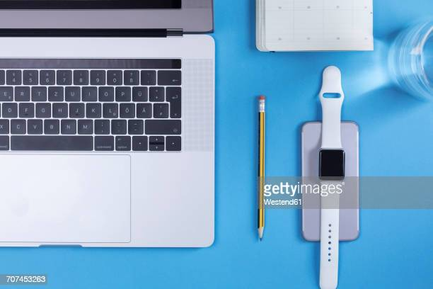 Various electronic devices, personal organizer, pencil and glass of water on blue ground