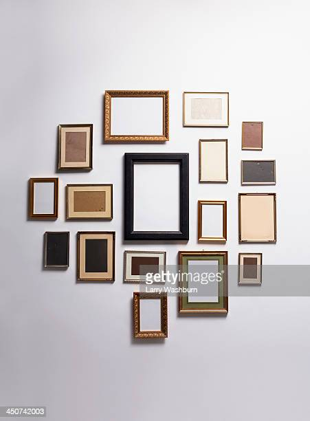 various empty picture frames hanging on a wall - 沢山の物 ストックフォトと画像