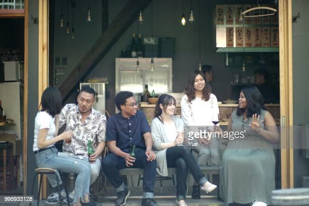 一緒に飲みを楽しむ様々 な民族の若者 - コミュニケーション ストックフォトと画像