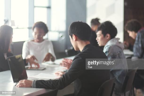 現代シェア オフィスで働く様々 な民族の若者 - ミーティング ストックフォトと画像