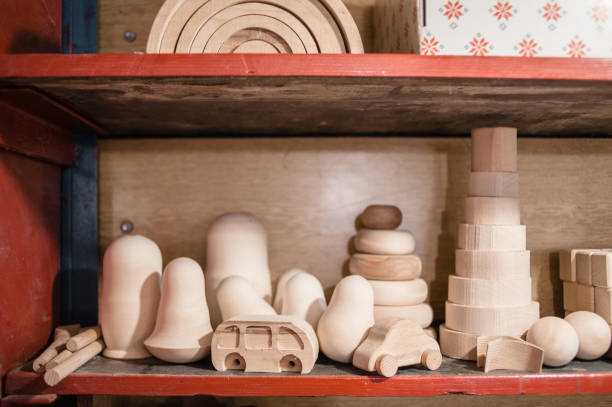 Various figures carved from wood stand on shelves in a toy workshop. Wooden toy blanks. Pyramid, rainbow constructors, rattles, roly-poly, toy cars.