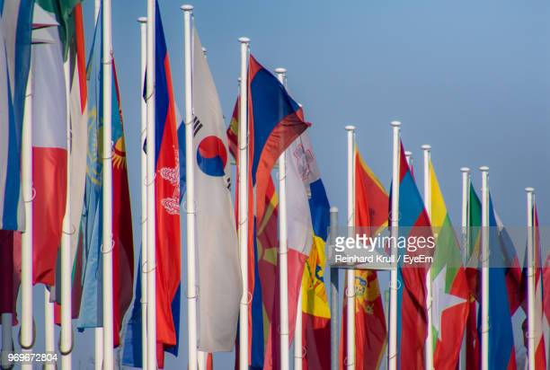 various flags against blue sky - national flag stock photos and pictures