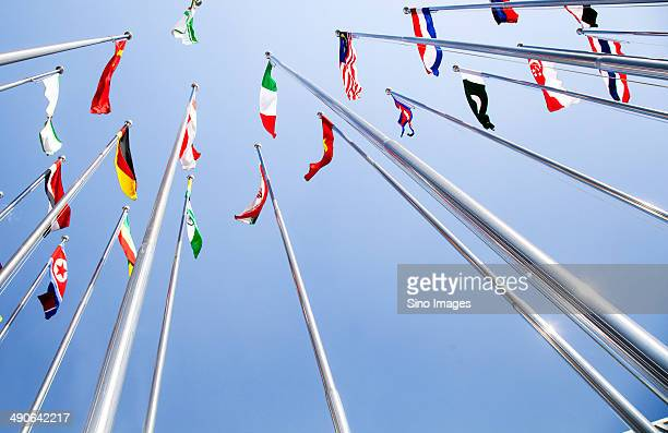 Various Flags Fluttering with Wind Under Blue Sky