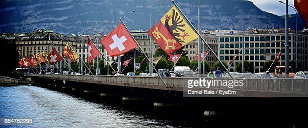 Various Flags On Bridge Over River In City