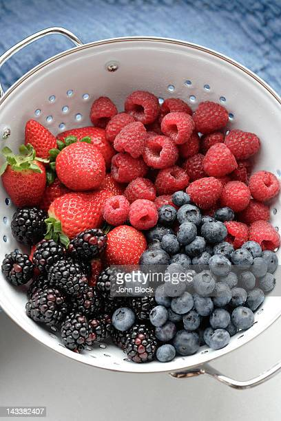 various fresh berries in colander - berry fruit stock pictures, royalty-free photos & images