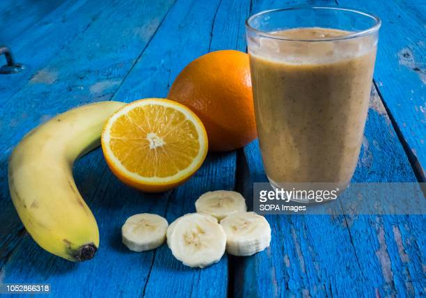 Various fruits and smoothie for weight loss seen displayed on a wooden background.