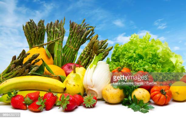 Various Fruits And Vegetables On Table Against Blue Sky
