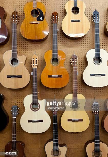 various guitars hanging from wall - ukulele stock-fotos und bilder