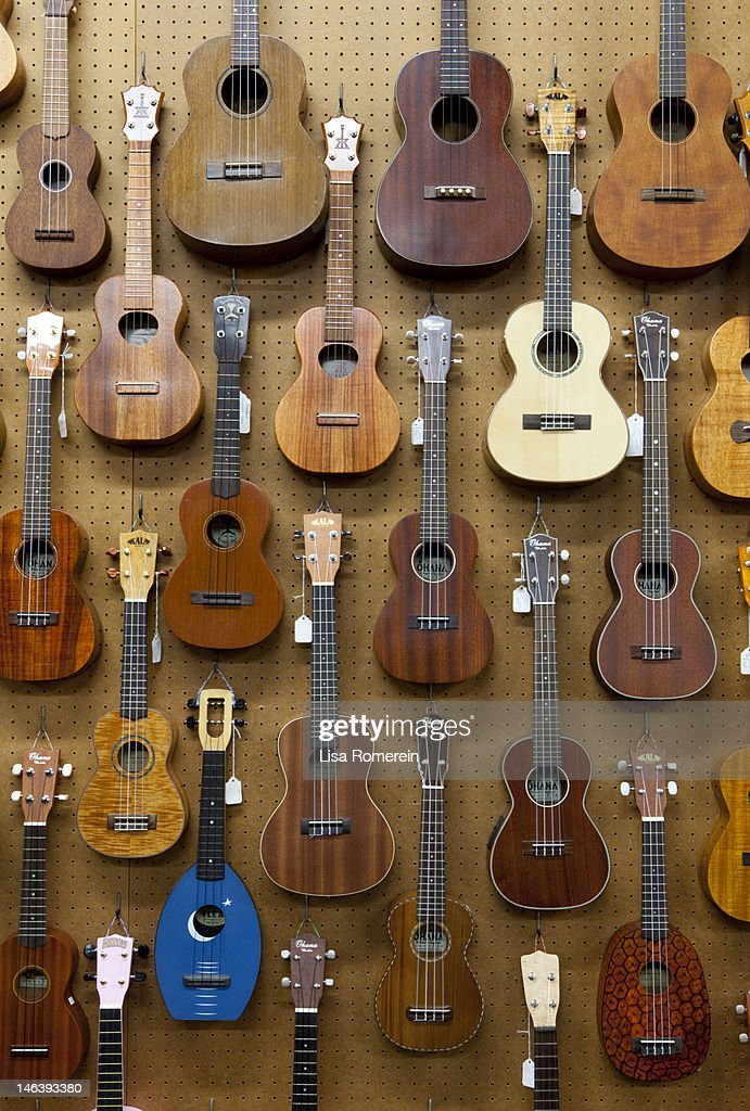 Various guitars & ukuleles hanging from wall : Stock Photo