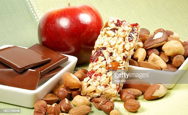 Various healthy snacks like an apple, granola bar and nuts
