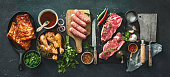 Various kinds of grill and bbq meats with vintage kitchen and butcher utensils