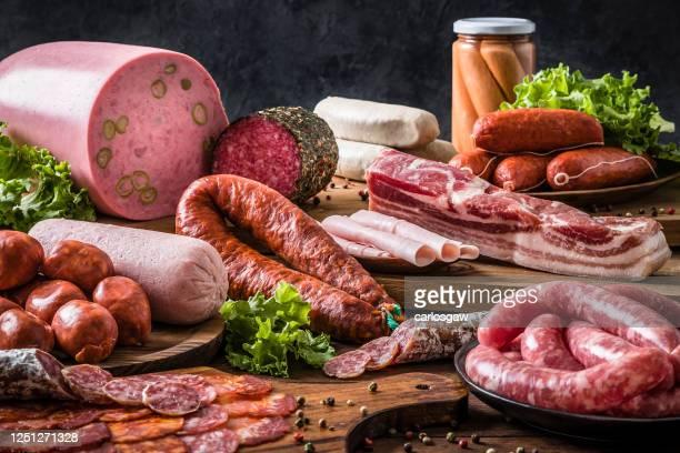 verschiedene arten von rohen würstchen auf einem rustikalen holztisch - fleisch stock-fotos und bilder