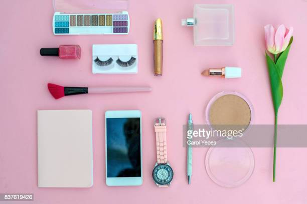 various makeup products and cosmetics in pink background.Top view