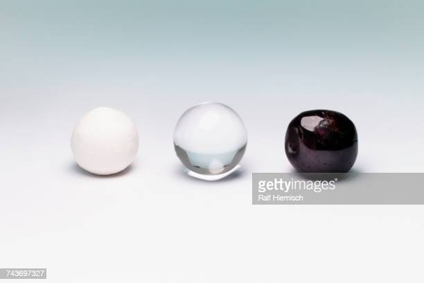 Various marbles arranged on white background