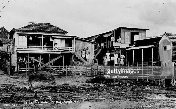 Various men and a couple of women stand around outside the ramshackle wooden Los Banos Hotel near the hot springs Los Banos Laguna Philippines
